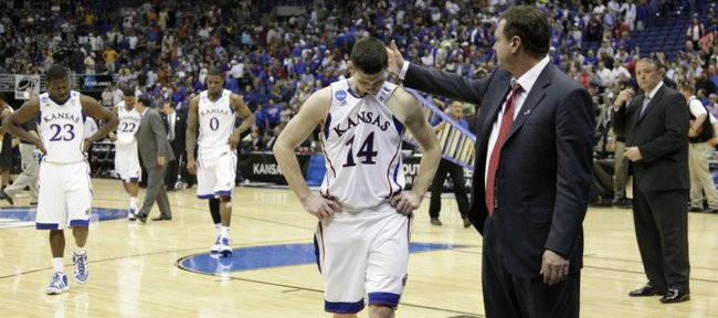 Kansas head coach pats senior guard Tyrel Reed on the as the Jayhawks leave the court after falling to Virginia Commonwealth on Sunday, March 27, 2011 at the Alamodome in San Antonio.