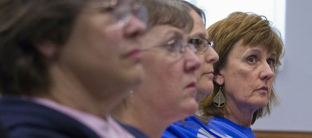 Bernie West, right, listens during a school board public hearing Monday regarding the proposal to close Wakarusa Valley School. West is a third-grade teacher at Wakarusa Valley, where she has worked for 28 years. The board voted 6-1 Monday to close the school, with only board member Marlene Merrill in favor of keeping it open.