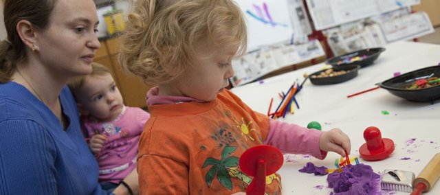 Lidiya Fulmer, Lawrence, holds 13-month old Victoria Fulmer while her daughter Anna, 2, works with purple PlayDo at the Lawrence Arts Center, 940 N.H. The arts center is commemorating the 25th year of its preschool program with a special exhibit of work by current and former students.