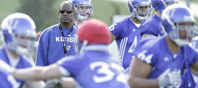 Kansas University head football coach Turner Gill watches over spring workouts at the practice facility on Friday, April 1, 2011.