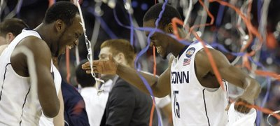 Connecticut&#39;s Kemba Walker, right, celebrates with teammate Charles Okwandu, left, at the end of the men&#39;s NCAA Final Four college basketball championship game against Butler Monday, April 4, 2011, in Houston. Connecticut won 53-41.