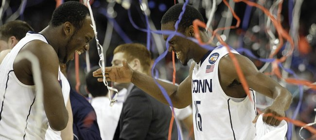 Connecticut's Kemba Walker, right, celebrates with teammate Charles Okwandu, left, at the end of the men's NCAA Final Four college basketball championship game against Butler Monday, April 4, 2011, in Houston. Connecticut won 53-41.