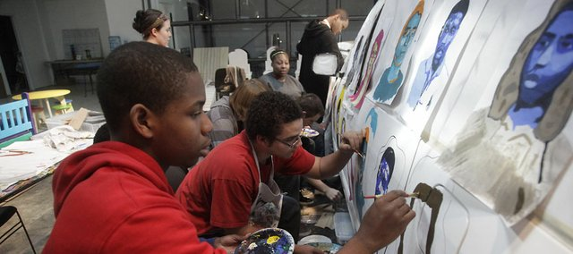 From left, artists Garnel Williams, 17, and Kamil Williams, 16, work on a new Van Go van, on Monday, April 4, 2011, which was revealed later in the month. Van Go is one of five Douglas County organizations that had its state funding from the Juvenile Justice Authority completely cut for the 2012 fiscal year.