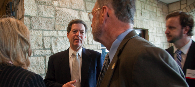 Governor Sam Brownback greets attendees at the KU Energy Conference Thursday, April 14, 2011. From left are Susan Duffy, Kanas Corporation Commission, Brownback, State Rep. Tom Sloan and Jeremy Viscomi, with the KU Tertiary Oil Recovery Project. Brownback spoke at the conference about the state's energy policy.