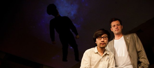 """Shanghai-based artist Jin Shan is pictured withKris Imants Ercums, curator of global, contemporary and Asian art at the Spencer Museum of Art, underneath Shan's installation titled """"It Came from the Sky."""" The installation, which features a 7-foot silicon policeman dangling below an image of space to Ercums, """" a playful critique of what is a police state in China."""""""