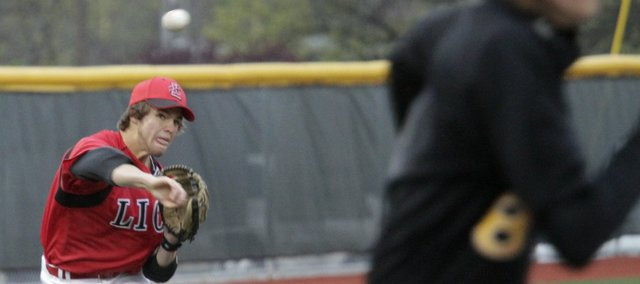 Shane Willoughby, left, throws out a runner in the Lions' meeting with Shawnee Mission West. The Lions beat the Vikings, 9-3, on Tuesday, April 19, 2011 at LHS.
