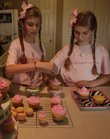 Liliana and Ella Keathley-Helms decorate cupcakes similar to ones they'll later sell for charity. The twins are holding an online bake sale for Mother's Day to raise money for children in Uganda.