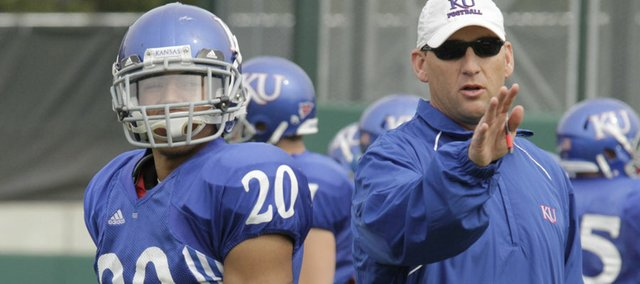 Kansas University wide receivers coach David Beaty, right, delivers instructions to KU wideout D.J. Beshears on April 18 at the KU practice field. Beaty rejoined the Jayhawks' staff after serving as offensive coordinator at Rice last season.
