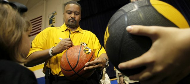 In this April 28, 2011 photo, Missouri mens basketball coach Frank Haith signs a basketball for a young fan at a Tiger Caravan event in Mendon, Mo.