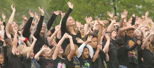 Schwegler School students and staff wave to artist Daniel Dancer as he is lifted in the air (not shown) to photograph everyone in the image of a western Meadowlark. The image was chosen to help celebrate Kansas' 150th birthday.