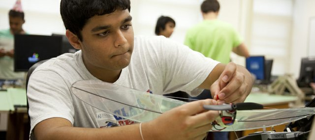 "Lawrence High senior Neel Patel puts the finishing touches on a model airplane he designed in an engineering class at LHS Friday, May 13, 2011, his final day of high school. Patel plans to socialize with his friends in the two weeks until graduation, which he admits will feel ""kind of weird."""
