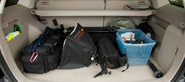 The newer used vehicle allows me to organize and pack light cases, soft box, tripod, reflector disk, light stand bag,  monopod and a plastic container for odds and ends more neatly in the back area under a roller shade.  Side pockets store reflected safety vest and rain gear.