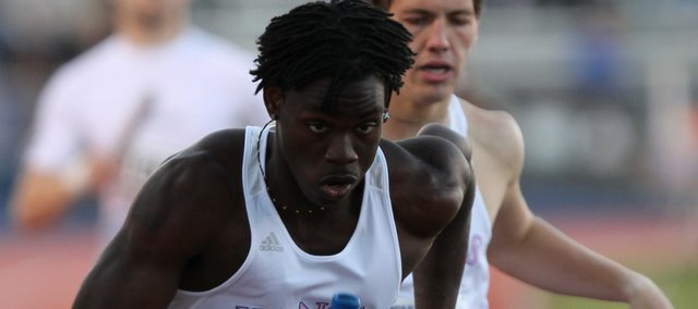 Kansas runner Keron Toussaint takes off as the anchor in the final heat of the men's 4x400-meter relay preliminaries after receiving the baton from Dalen Fink on Friday, April 22, 2011 at the Kansas Relays.