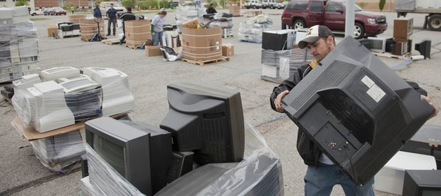 A Surplus Exchange company employee unloads a television during the Lawrence Electronic Recycling Event at Free State High school Saturday, May 14, 2011. The Surplus Exchange from Kansas City, MO., collected the equipment which will be kept out of landfills and either recycled in an environmentally friendly way or entered into one of their reuse programs.