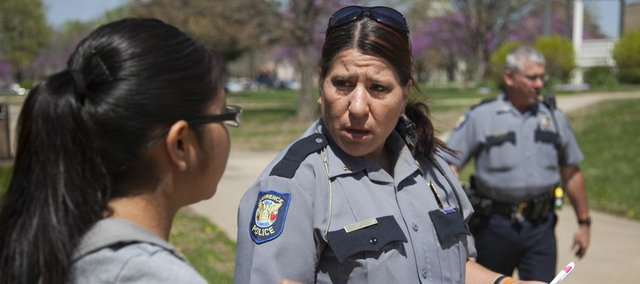 Lawrence police officer Laurie Scott, center, takes information from Haskell student Joelle Mansfield while investigating a report on a possibly stolen bike that was found locked in front of Tommaney Library Tuesday, April 12, 2011.
