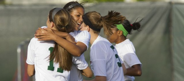 Free State sophomore Margaux Gill hugs teammate Madeline Dieker (11) following Dieker's goal against Junction City. The Firebirds rolled, 9-1, on Tuesday, May 17, 2011 at FSHS.
