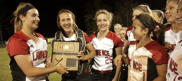 Lawrence High players, from left, Lauren Massey and Kristen Bell hold the trophy and celebrate with Rachel Kelly (25), Marly Carmona (1) and other teammates after their victory over Topeka High in the regional championship. The Lions won, 12-10, Tuesday in Topeka to advance to state.