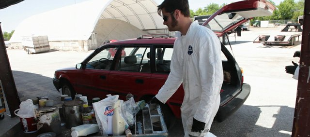 Tom Hogan, waste reduction and recycling specialist at the Lawrence/Douglas County Household Hazardous Waste Facility, carts away dropped-off household waste May 20, 2011.