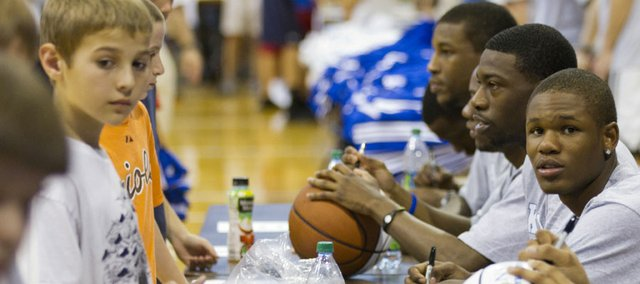 Kansas University freshman Ben McLemore, right, observes the campers during Bill Self's basketball camp on Sunday, June 5, 2011 at Allen Fieldhouse. Next to McLemore is KU junior guard Elijah Johnson.
