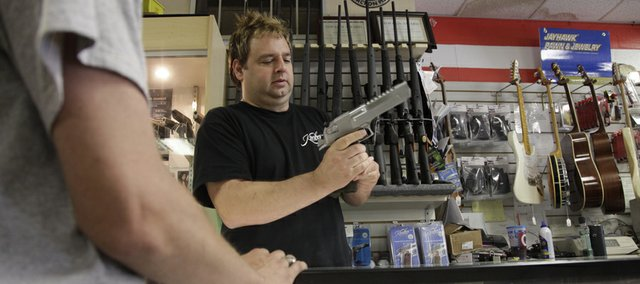 John Geery shows a gun to a customer at Jayhawk Pawn and Jewelry, 1804 W. Sixth St., Monday, June 6, 2011.