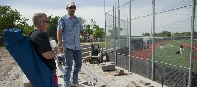 Brian Pope, father of a Free State baseball player, left, visits with Chris Culp with Lawrence Landscape, as Culp and a crew install new Versa-Lok block bleachers at the Free State High School baseball field on Friday.  New bleachers will be installed for soccer and baseball at both high schools and also for softball at Free State. Lawrence High also will be getting donor-financed upgrades at field entrances and around scoreboards. Schools across the district are also undergoing remodeling to create or upgrade classroom spaces.