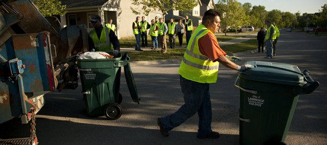 John Harjo pushes a trash bin while members of the city's Solid Waste Task Force observe, Tuesday, May 17, 2011. The task force took a tour to learn more about of Lawrence trash and recycling operations.