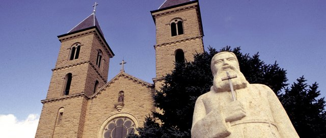 A limestone statue of a Capuchin friar stands in front of the twin towers of St. Fidelis Catholic Church at Victoria, in this undated file photo. The landmark, also known as the Cathedral of the Plains, draws about 16,000 tourists a year from nearby Interstate 70.