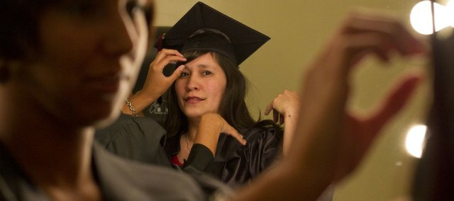 Darian Franks, left, of Lawrence, fixes Kristie Coffey's hair Thursday before the start of the Adult Learning Center GED graduation ceremony at Free State High School. The Adult Learning Center helped 88 students earn their GED diplomas.