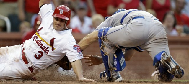 St. Louis shortstop Ryan Theriot, left, is tagged out by Kansas City catcher Matt Treanor. Nonetheless, the Cardinals defeated the Royals, 5-4, on Saturday in St. Louis.