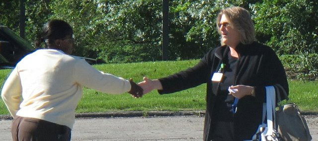 An employee of a Planned Parenthood clinic, left, greets an inspector from the Kansas Department of Health and Environment, Wednesday, June 22, 2011, outside the clinic in Overland Park, Kan. The department is inspecting the clinics under a law enacted this year mandating health and safety standards and a special licensing process for abortion providers.