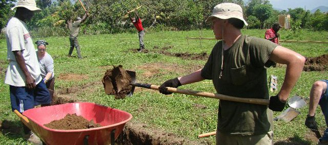 Scott Lamb and Beth Knapik, members of Lawrence's First Baptist Church, dig the foundation of a school in Cap-Haitien, Haiti, on a mission trip.