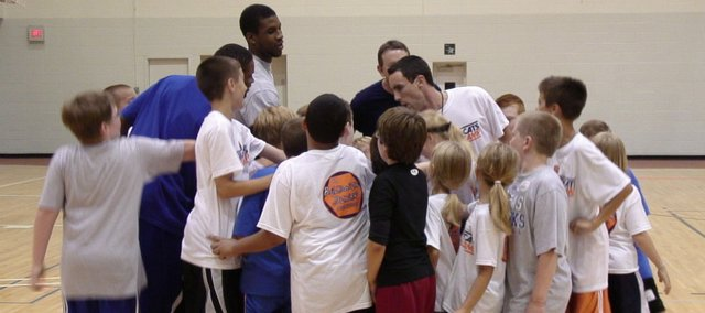 Baker head men's basketball coach Brett Ballard huddles up with players during his basketball camp Thursday, June 30, 2011 at Baker University. Kansas players Thomas Robinson, at left in gray shirt, and Ben McLemore, at left in blue shirt, were counselors at the camp.