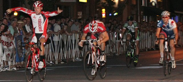 Andrew Dahlheim, left, of Bissell Pro Cycling, crosses the finish line first to win the Tour of Lawrence men's street sprints. Spectators lined New Hampshire Street, between Seventh and Eighth streets, to watch the races on Friday, July 1, 2011, in downtown Lawrence.