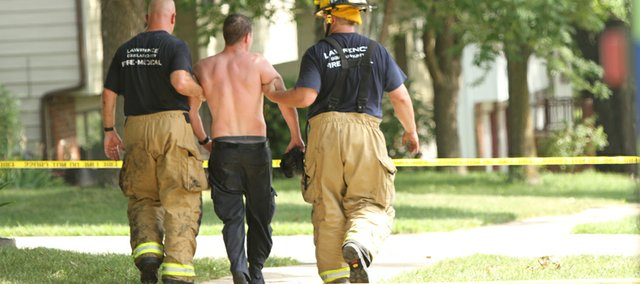A Lawrence Douglas County Fire & Medical firefighter is led away from the scene of a house fire in west Lawrence on Tuesday, July 5, 2011. Two people were taken to Lawrence Memorial Hospital with injuries, including one firefighter who suffered from heat exposure. There was no word immediately available as to the cause of the fire or the value of the damage.