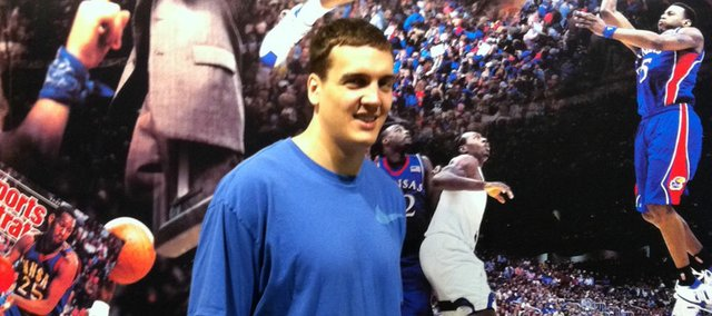 Former Kansas University center Sasha Kaun walks in front of the KU basketball mural on Thursday outside the Northwest tunnel of Allen Fieldhouse. Kaun has been in town visiting for about a week.