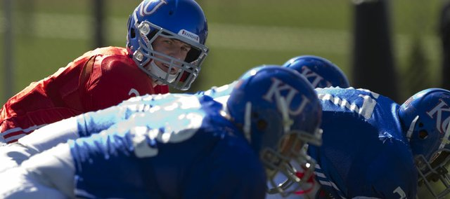 Kansas quarterback Jordan Webb looks down the line as he runs through drills during practice on April 11 at the practice fields near Memorial Stadium. A third-year sophomore, Webb emerged from spring drills as the narrow leader for the starting QB job this fall.
