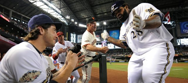 Milwaukee slugger Prince Fielder, right, is congratulated by San Francisco manager Bruce Bochy, middle right, and Brewers teammate Ryan Braun, left, after hitting a three-run home run in the fourth inning. Fielder's homer sparked the National League to a 5-1 victory over the American league on Tuesday in Phoenix.