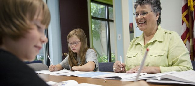 International student evaluator Jon K. Murphy, right, works with Sasha Givotovsky, 11, left, and his sister Nina, 13, center, with some English as a Second Language screening tests Tuesday, July 12, 2011, at the school district's Welcome and Enrollment Center.