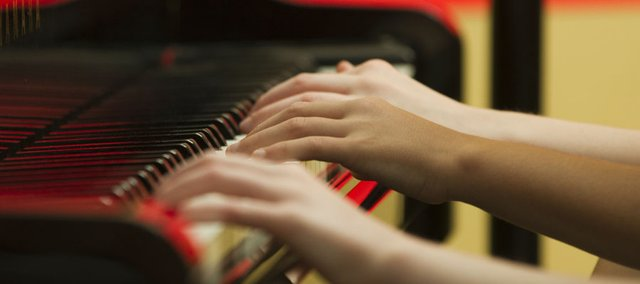 Piano students practice playing with their left hands June 23 at piano instructor Karla Grether's home. Grether is using a teaching method called Simply Music, which teaches students to play without first having to learn how to read music.