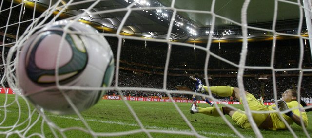 Japan's Saki Kumagai, background, scores the decisive goal past United States goalkeeper Hope Solo during the penalty shootout of the Women's World Cup championship on Sunday, July 27, 2011 in Frankfurt, Germany.