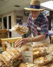 Lawrence resident Chuck Benedict, 85, stacks loaves of donated bread along a table at the Douglas County Senior Center on Wednesday, July 13. Benedict says he's been delivering the bread for about four years, picking up donations from the Clinton Parkway Hy-Vee store and from Checkers to distribute to local seniors.