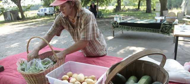 Brady Karlin of Karlin Family Farms is the creator of a weekly barter market known as the F.U.N. FARMily Fair. Here, he sets out vegetables for the fair, which runs from 4:30 to 7:30 p.m. Fridays at his farm, 3033 Kasold Drive. Visitors are encouraged to bring items to exchange for items they need or pay what they think available products are worth to them.