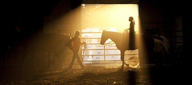 Regan Zaremba, 13, right, and Kelly Loganbill, Lawrence, cross through a shaft of light entering the livestock arena during practice July 19, 2011, at the Douglas County 4-H Fairgrounds. The fair's annual barrel racing event starts at 7 p.m. Friday.