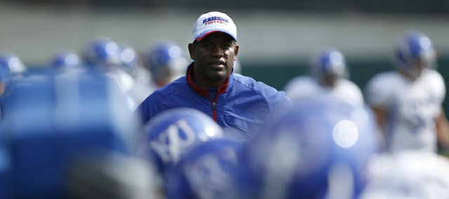 Kansas head coach Turner Gill watches as the defense works out on the sleds during football practice on Monday, April 18, 2011 at the practice fields near Memorial Stadium.