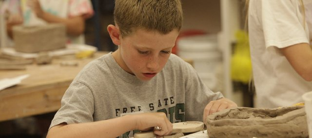 Jacob Gillespie, 12, shapes a clay vessel at the Lawrence Arts Center in a Sculpting with Clay class offered through the center's new Arts Institute.