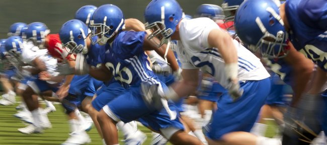 Running back Deshaun Sands bursts off the line as the Jayhawks run sprints during the team's first practice on Thursday, Aug. 4, 2011.