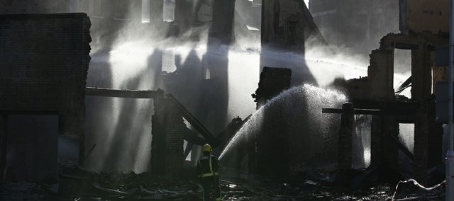 A firefighter sprays water on the furniture store set on fire by rioters last night in Croydon, south London, Tuesday, Aug. 9, 2011.A wave of violence and looting raged across London and spread to three other major British cities Tuesday, as authorities struggled to contain the country's worst unrest since race riots set the capital ablaze in the 1980s.