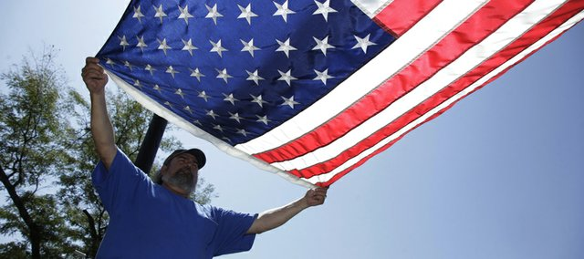 KU Facilities and Operations worker Ed Kiernan gets ready to fold the American flag at Strong Hall July 29, 2011.