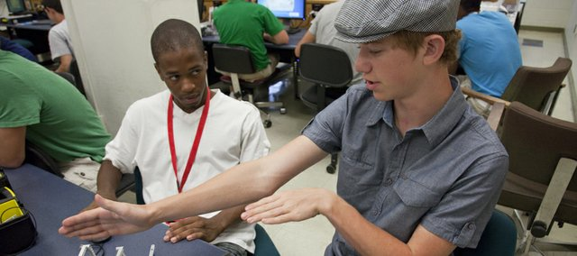 Demetrius Ruffin, left, and Alex Wilson, both 15, discuss how they need to program their robot for the next round. Groups of young engineers went head to head in a battle of robots and tennis balls during a summer engineering camp at Learned Hall.