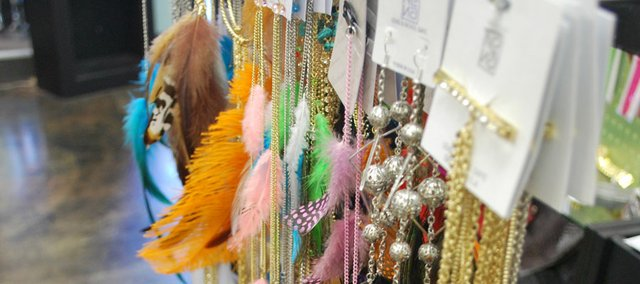 "Jessie Plotkin, the manager at Envy, 911 Mass., says that feather earrings are the hottest item in their shop right now. ""Each week we sell out of the feather hair extensions, and the earrings are also popular. Many girls wear one long feather earring and one stud earring."""